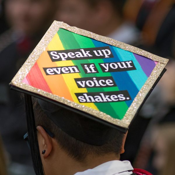 "A young man wears a mortar board that reads ""Speak up even if your voice shakes."""