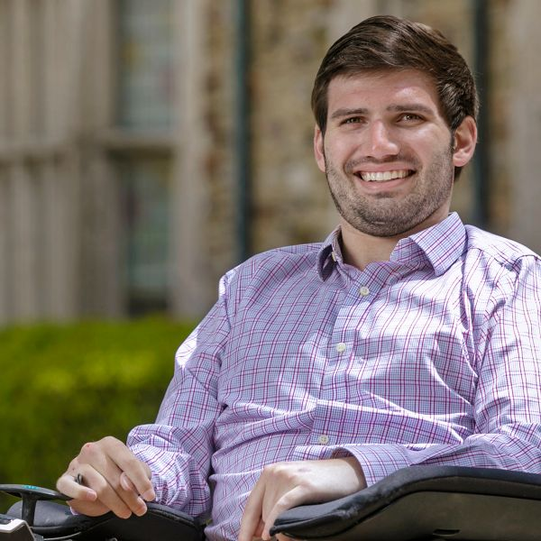 A dark haired young man with a wide smile looks into the camera from his motorized wheelchair.