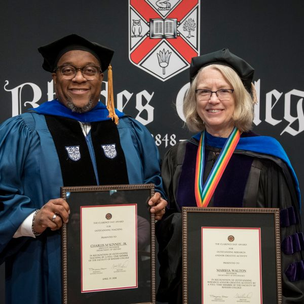 Two professors in regalia stand side by side with their distinguished awards.