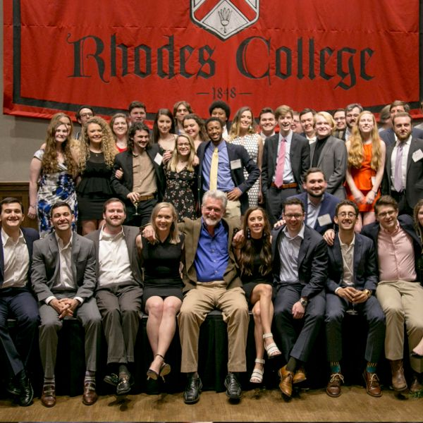 A group of alumni seated in rows in front of a Rhodes College banner.