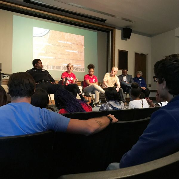 A group of professors, students, and activists sit in a panel discussion in front of an audience in a small lecture hall.