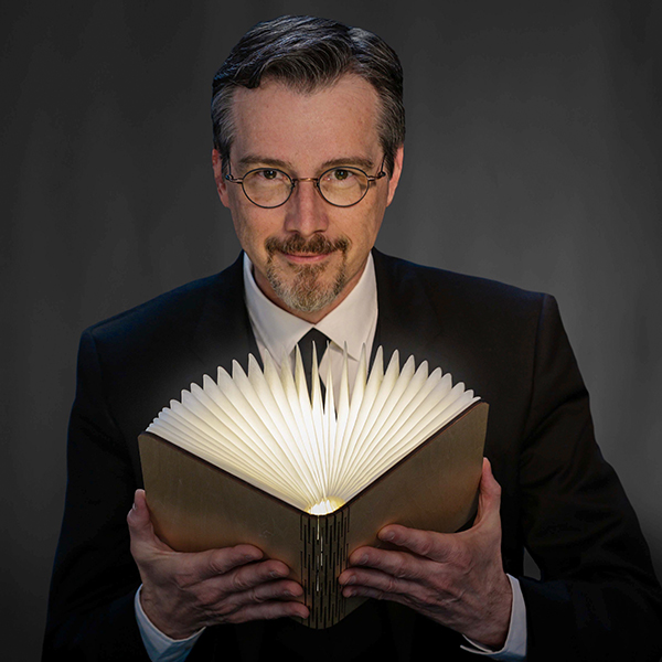 portrait of Dr. Lawrence Hass holding book