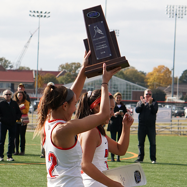 a female field hockey player holds up a trophy