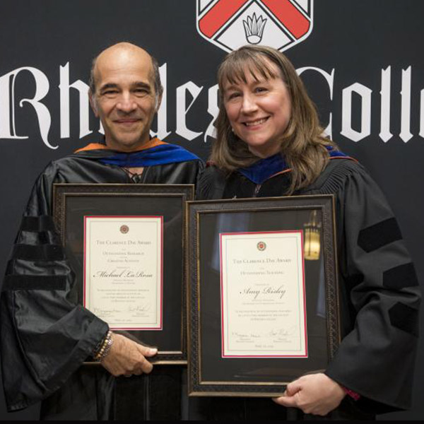 a male and female professor in academic robes, holding awards