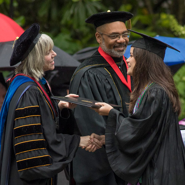 President Hass hands a diploma to a graduating senior