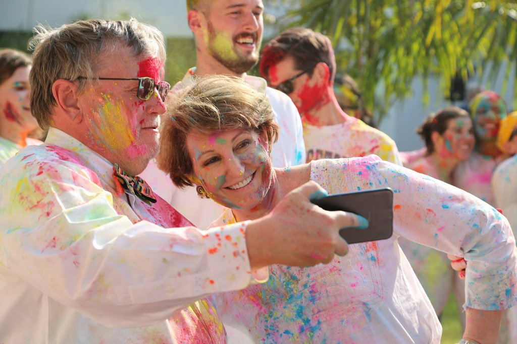 MaryKay Carlson covered in colorful powder at a Holi celebration