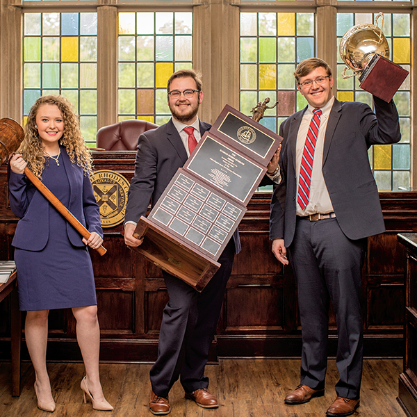 three students hold up mock trial trophies