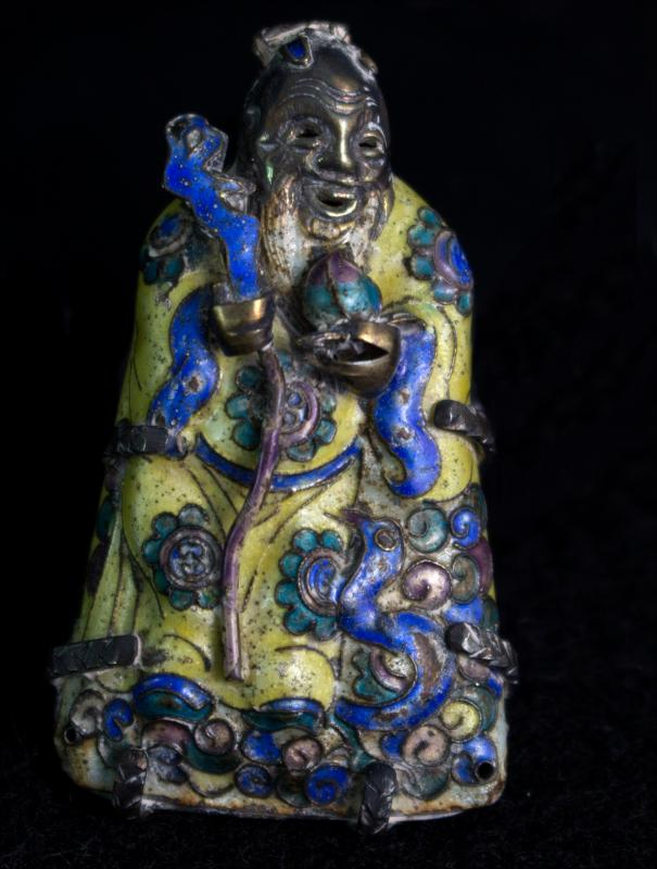 a small blue and green figurine of a woman