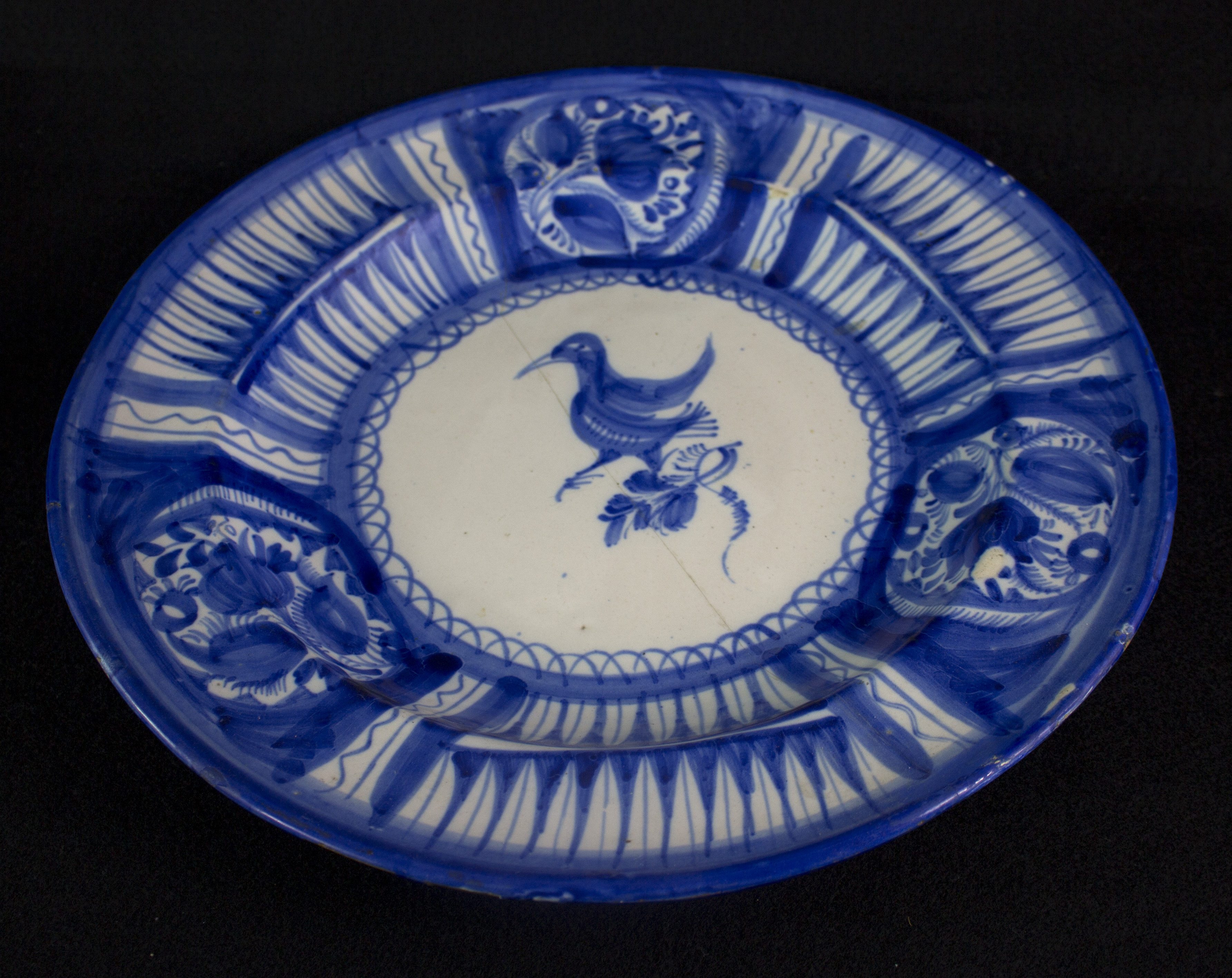 a blue and white plate with the image of a duck