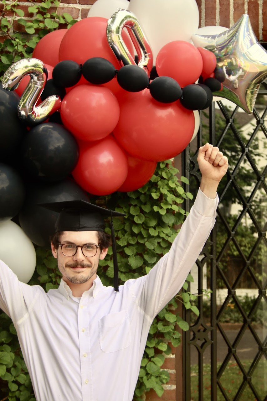 a young an wearing a mortarboard raises his arms in front of balloons that spell out 2020