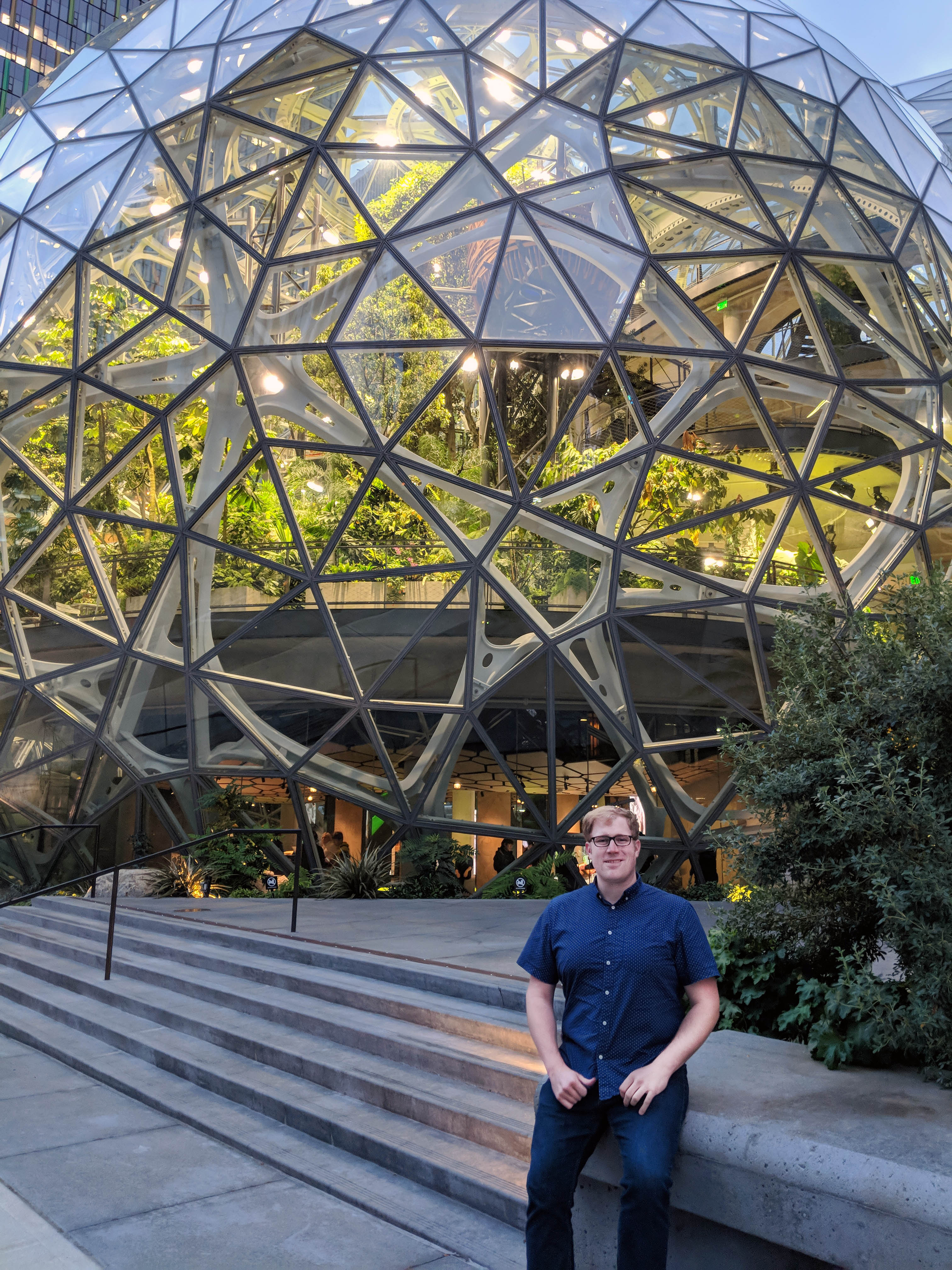 A man sits on steps in front of spherical glass and metals architecture on Amazon's campus