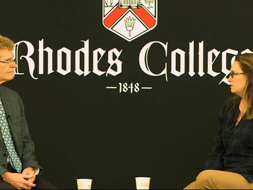 A man and woman sit across from each other in front of a black backdrop that displays the Rhodes College logo.