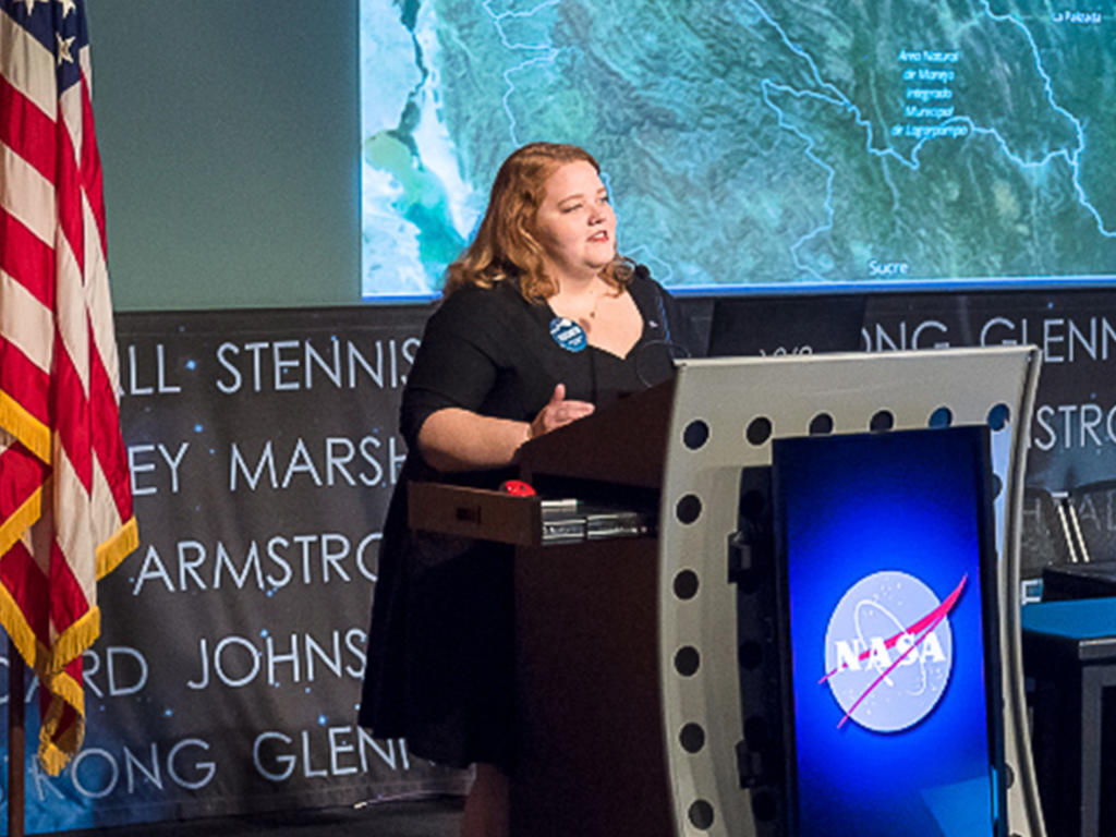 Woman stands at a podium that says NASA