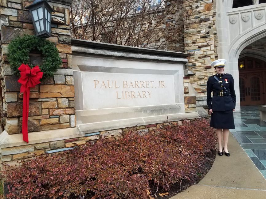 student in a marine uniform standing in front of a campus library sign