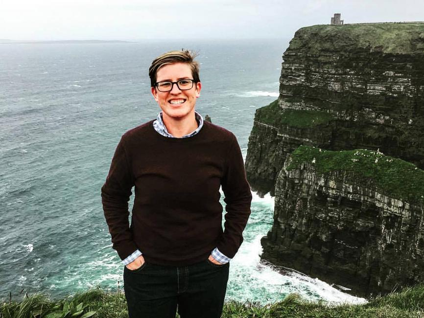 A woman with short hair stands on a cliff in front of the sea