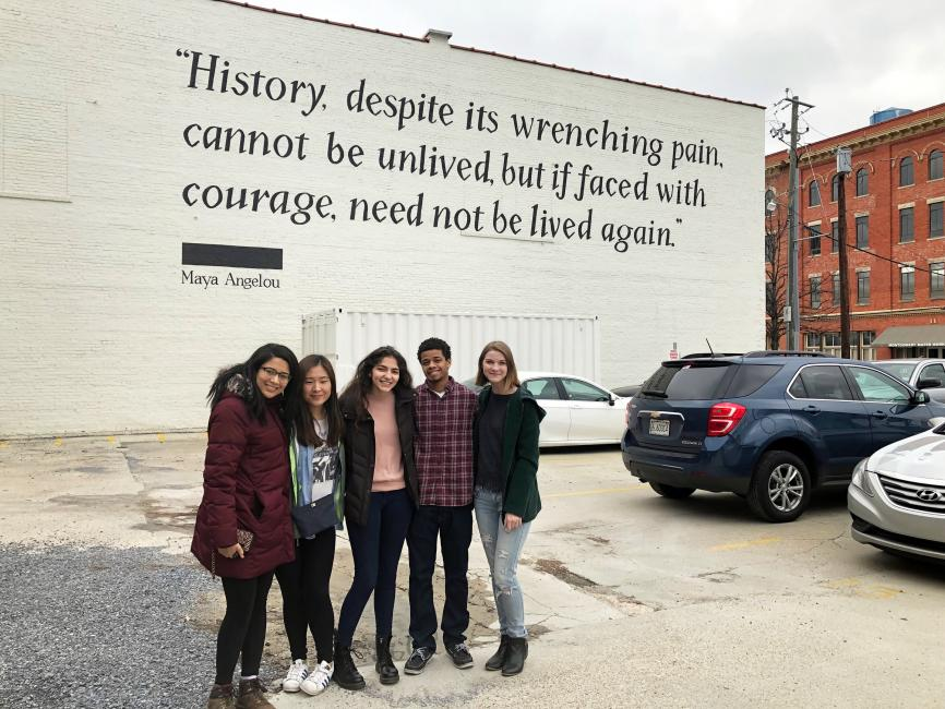 college students standing under quote written on building
