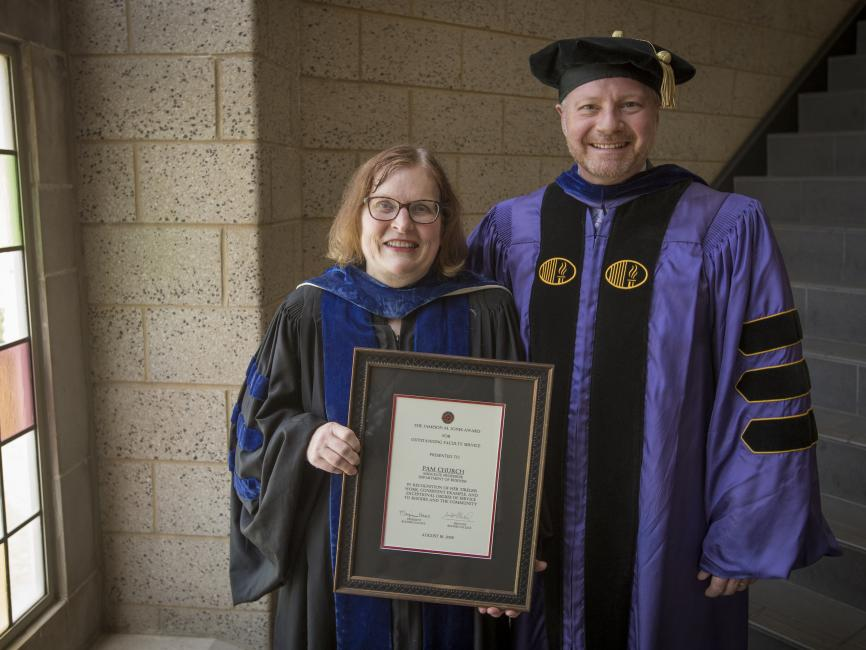 professor, standing next to a college administrator,  holding an award plaque