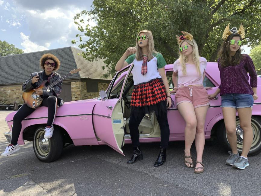 Four students dressed in costumes lean against a vintage car