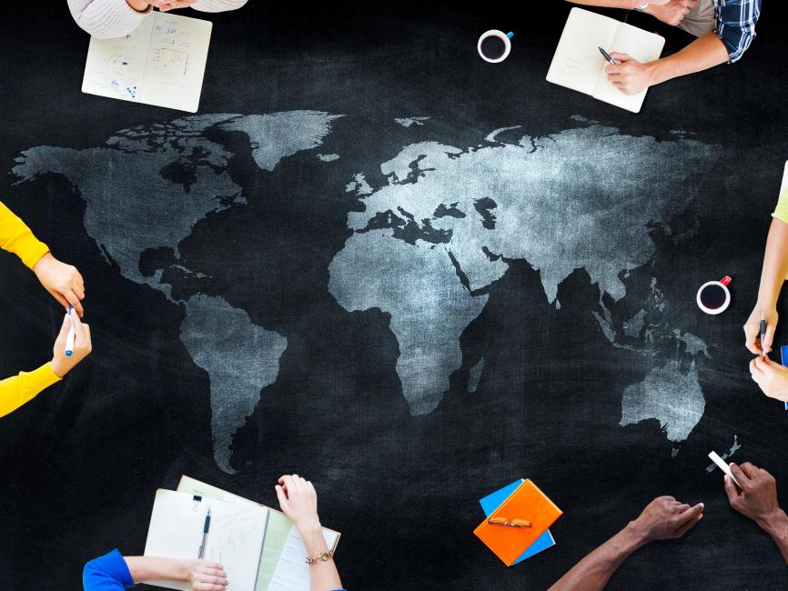 students gathered around a table with a map