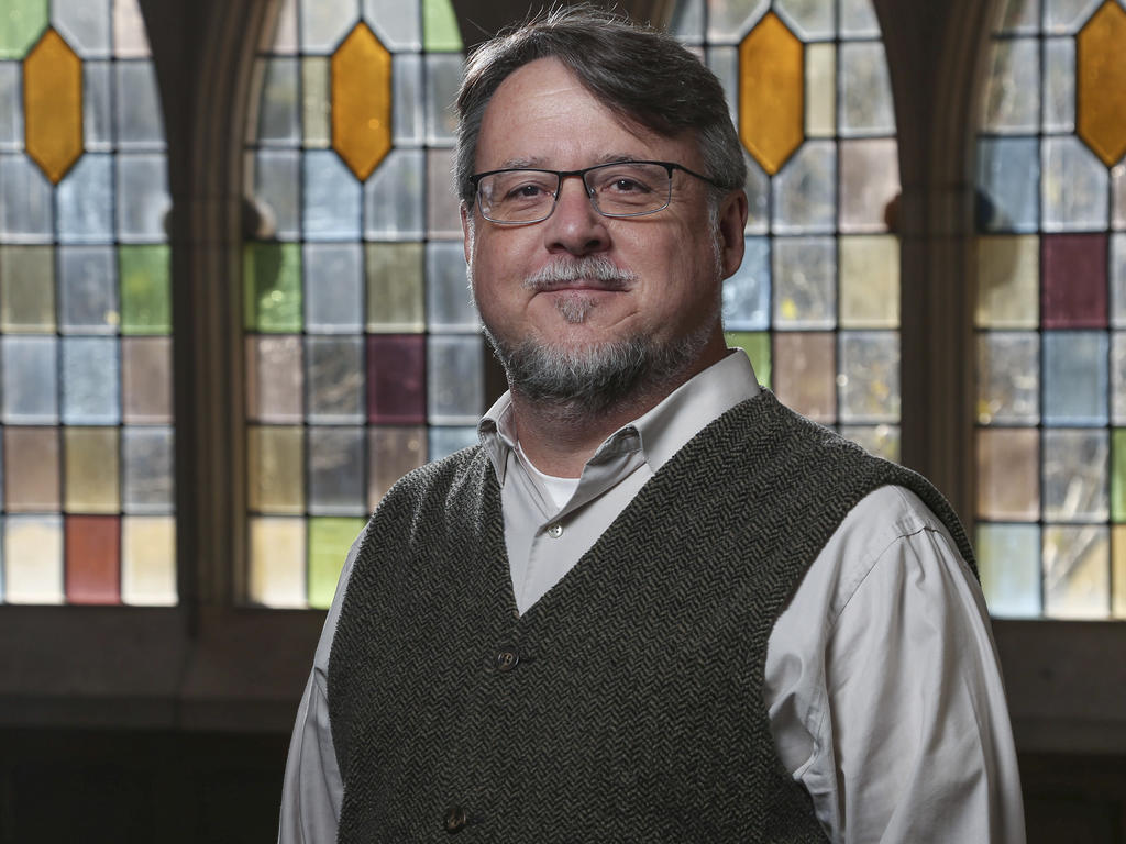 head and shoulder image of a college professor in front of a stained glass window