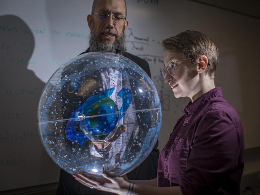 professor and student with globe