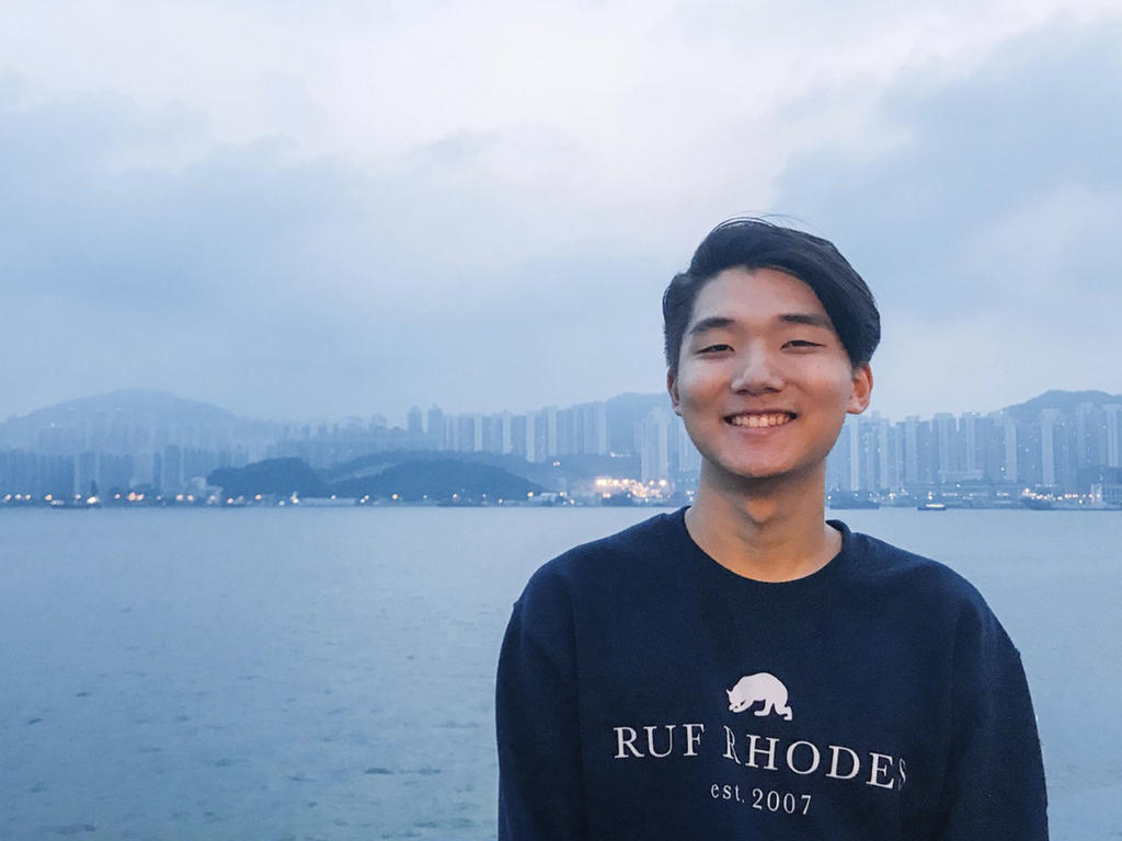 a young Asian male stands in front of a harbor surrounded by hills