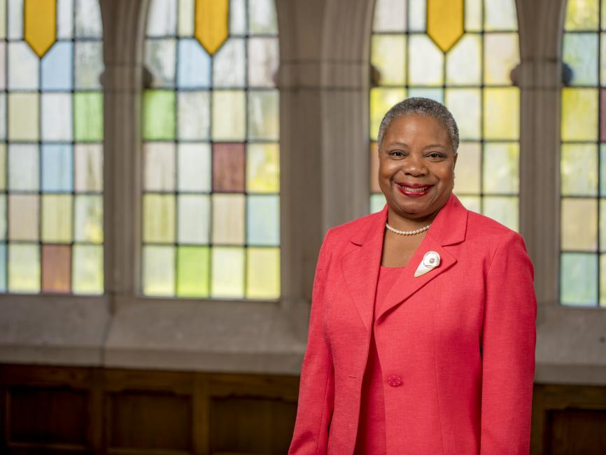 A person in a red suit smiles at the camera in front of stained glass windows