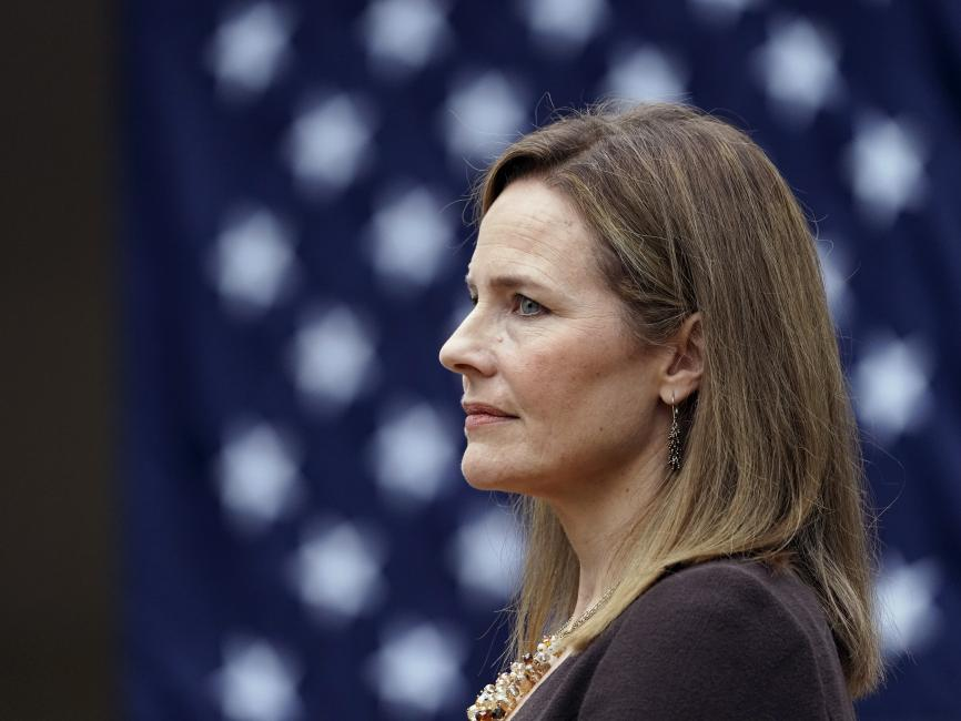 Judge Amy Coney Barrett '94, facing to right of frame, a field of white stars on a blue background behind her.