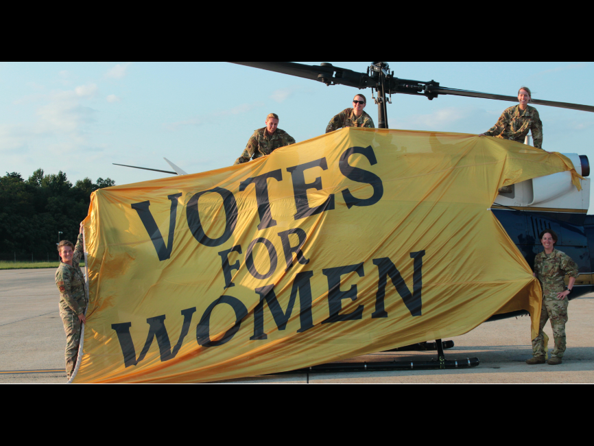 women in uniform hold up a banner