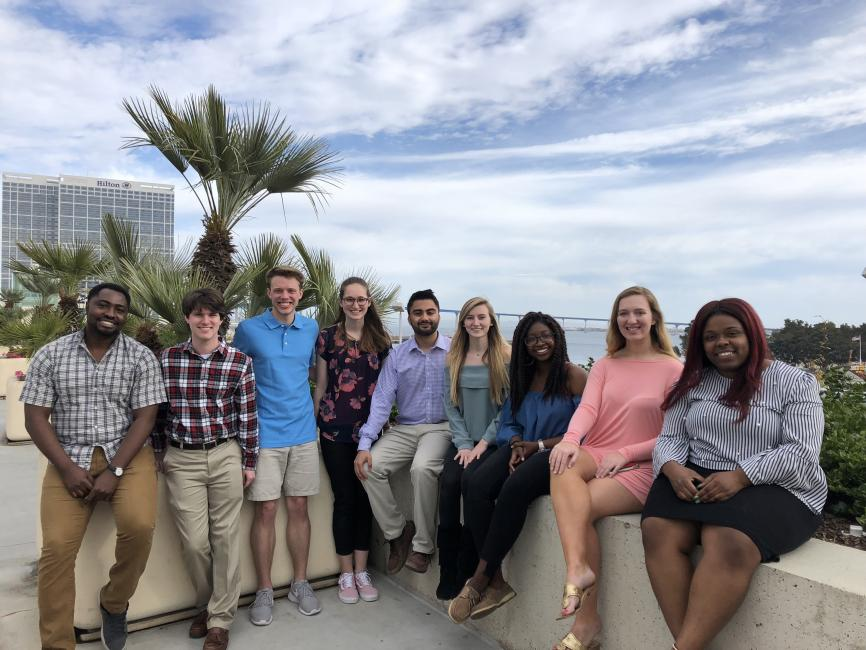 group shot of nine student scientists posing outside on a balcony; sky and ocean in the background
