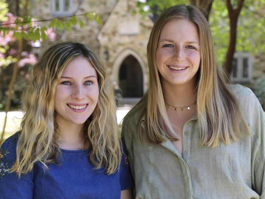 Two young female students in front of Buckman Hall
