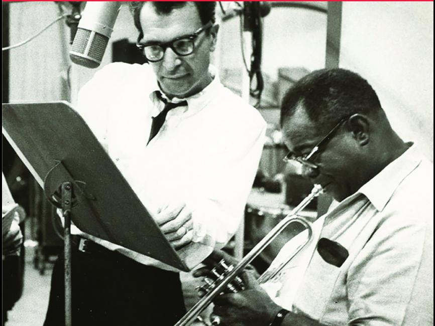 a black and white picture of jazz musicians reading music while playing their instruments