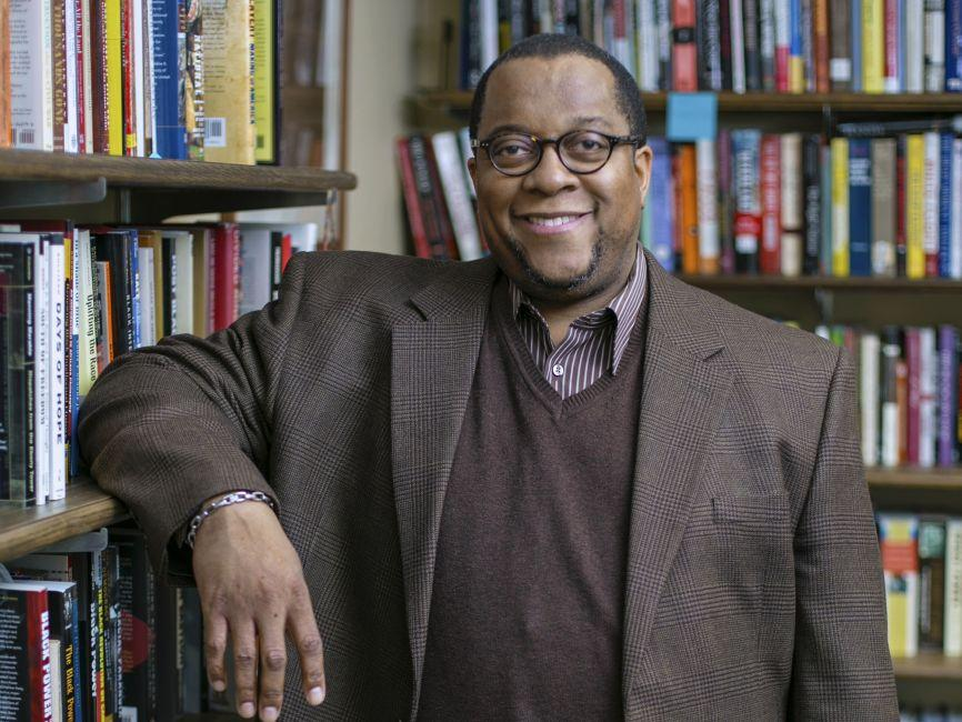 an African-American professor smiling and standing in front of a book shelf