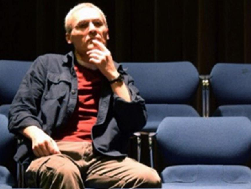 a man sitting pensively in theatre seats