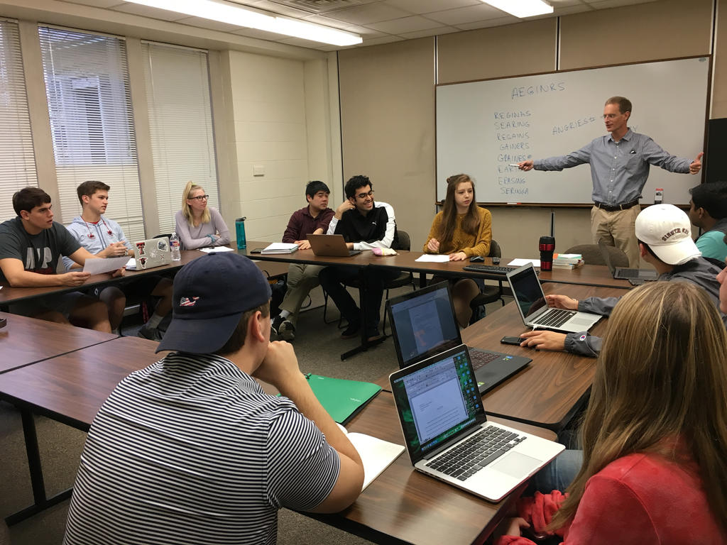 professor teaching college students in a classroom