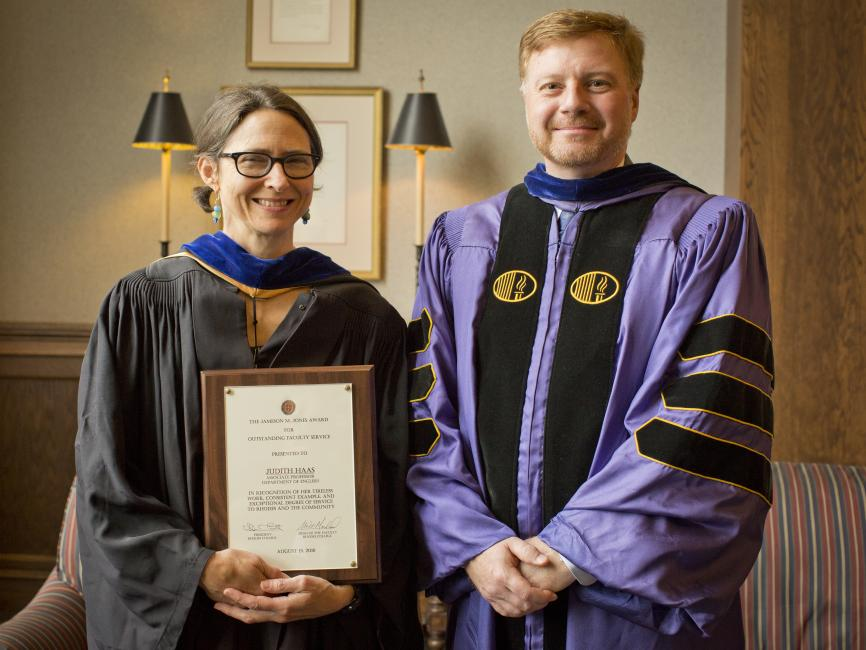 a female professor proudly holding her award next to the dean; both are sporting academic robes