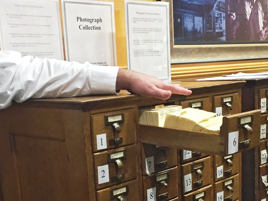 A hand resting above an open card catalogue