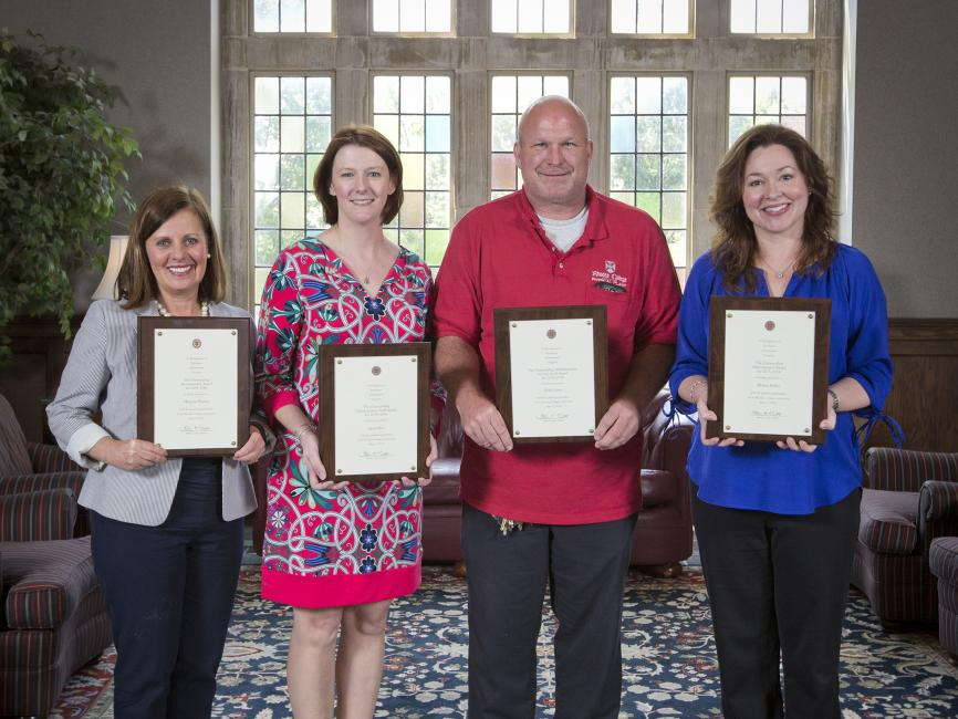 four faculty members proudly holding their framed awards