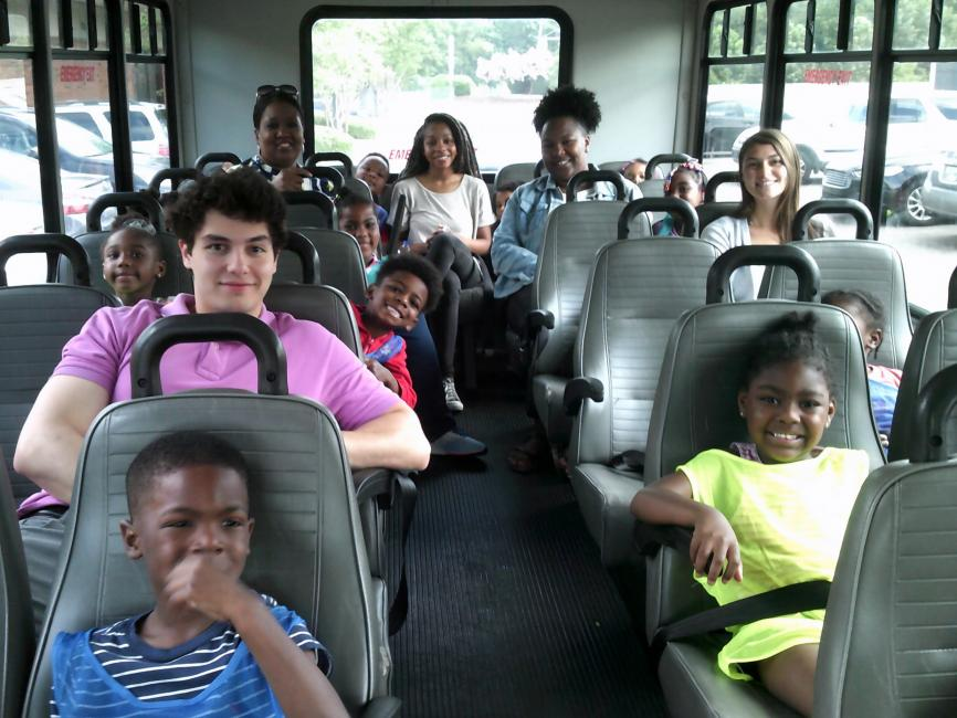 college students seated with pre-K children on a bus