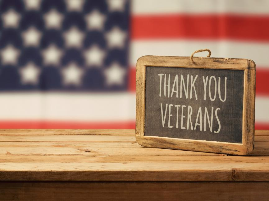 "sign saing ""Thank you veterans"" sits on a table in front of the U.S. flag"