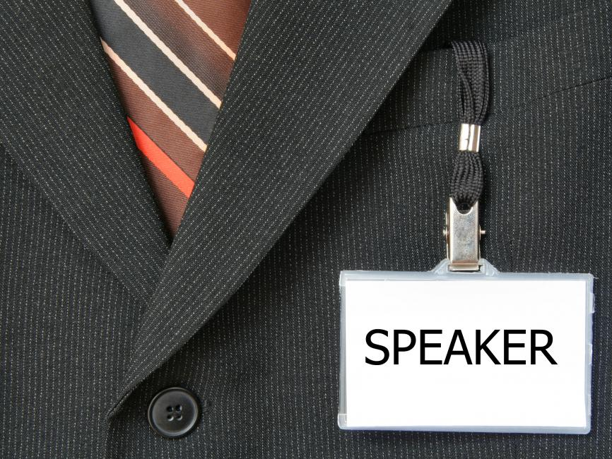 "a closeup of a tie tucked into a suit jacket with a name tag that says ""Speaker"" hanging from the collar"