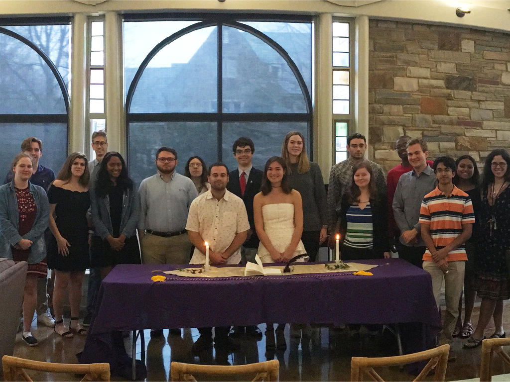 group of students standing at table with candles for an induction ceremony