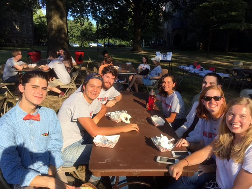 a diverse group of male and female students smiling at a picnic table