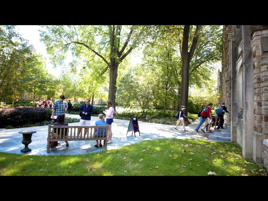 various students gathered on a quad, sitting in benches or socializing on a peaceful day